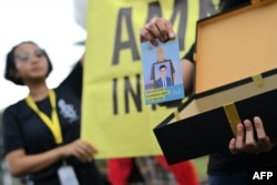Seorang aktivis Amnesty International dalam demonstrasi di luar Istana Kepresidenan di Jakarta, 10 Desember 2019. (Foto: AFP)