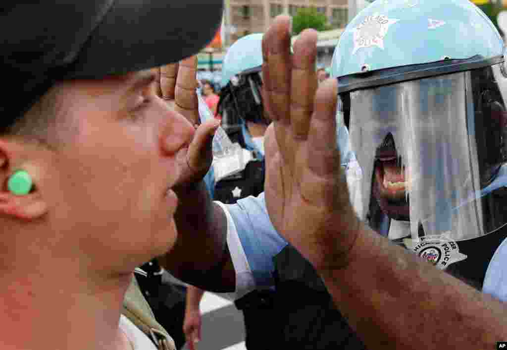 A Chicago Police officer confronts a protester during a march and rally at this weekend's summit. (AP)