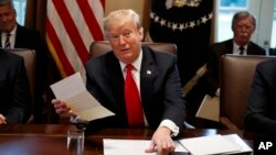FILE - President Donald Trump holds up a letter he says is from North Korean leader Kim Jong Un, during a cabinet meeting at the White House, in Washington, Jan. 2, 2019.