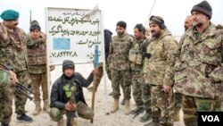 """Afghan security forces posing to camera in front of a so-called Afghanistan Islamic Emirates custom house sign the reads """"Do no pass without custom house tariff. Jan. 13. 2020. (Photo courtesy of Afghan Ministry of Defense)"""