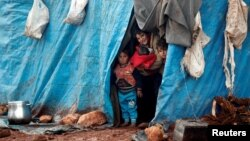 Displaced Syrian children look out from their tents at Kelbit refugee camp, near the Syrian-Turkish border, in Idlib province, Syria, Jan. 17, 2018.