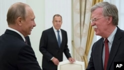 FILE - In this June 27, 2018 photo, Russian President Vladimir Putin, left, and U.S. National security adviser John Bolton greet each other as Russian Foreign Minister Sergey Lavrov looks on during their meeting in the Kremlin in Moscow.