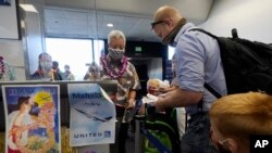 In this Oct. 15, 2020 file photo, a United Airlines agent checks in passengers at the gate to board a flight to Hawaii at San Francisco International Airport in San Francisco.(AP Photo/Jeff Chiu, File)