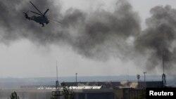 Sebuah helikopter pemerintah Ukraina menembak pemberontak di bandara Donetsk (26/5). (Reuters/Yannis Behrakis)