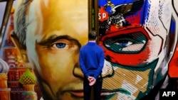 """Un homme regarde un tableau représentant le président russe Vladimir Poutine à l'exposition """"SUPERPUTIN"""" au musée de l'UMAM à Moscou le 6 décembre 2017"""