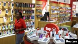FILE: A worker walks past cell phone accessories at a Vodacom shop in Johannesburg February 4, 2015.