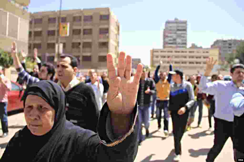 Protesters march through Cairo holding up four-fingers, a hand sign in memory of last year's deadly crackdown on supporters of ousted President Mohamed Morsi, March 28, 2014. (Hamada Elrassam/VOA)