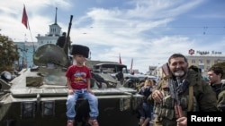 A boy sits on an armored personnel carrier (APC) as he poses for a picture during a parade in Luhansk, eastern Ukraine, September 14, 2014. Ukraine's Defence Minister said on Sunday that NATO countries were delivering weapons to his country to equip it to