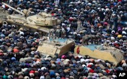 FILE - In this Feb. 11, 2011, photo, anti-government protesters, and Egyptian soldiers on top of their vehicles, make traditional Muslim Friday prayers at the continuing demonstration in Tahrir Square in downtown Cairo, Egypt.