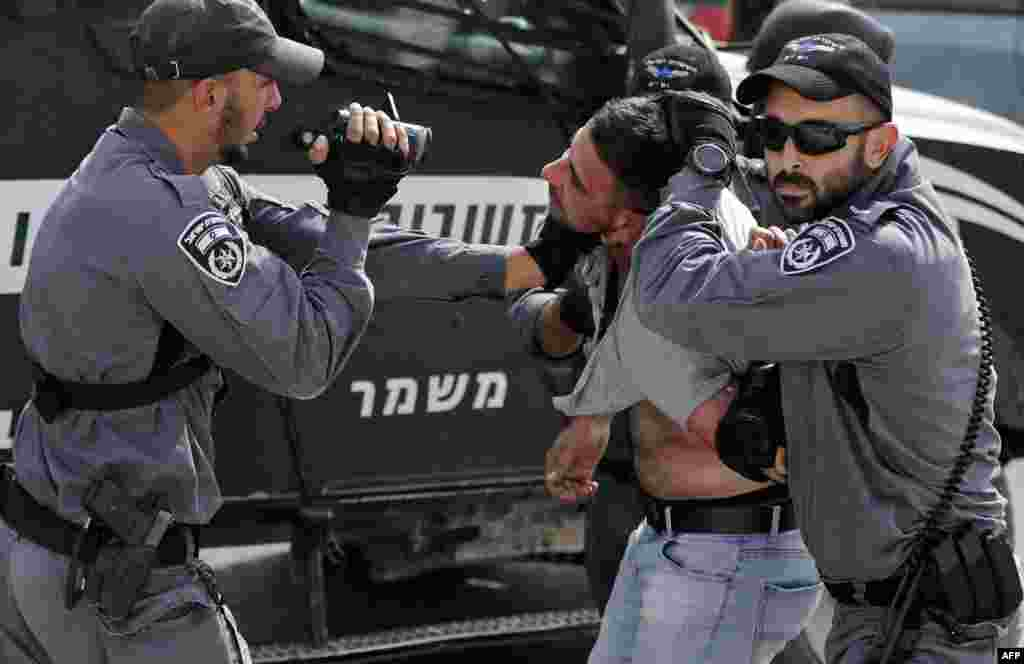 An Israeli policeman films a Palestinian as others hold him for detention during a demonstration at the Palestinian Bedouin village of Khan al-Ahmar, east of Jerusalem in the occupied West Bank and which Israel plans to demolish.