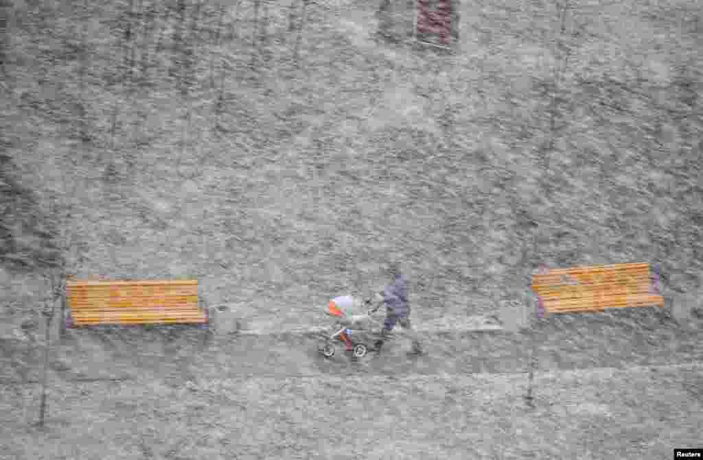 A man with a pram walks during heavy snowfall in Minsk, Belarus.