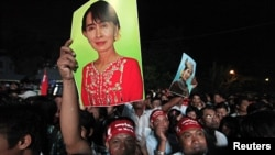 Supporters celebrate holding posters of Aung San Suu Kyi as election results are displayed on a screen in front of Burma's National League for Democracy head office in Yangon April 1, 2012.
