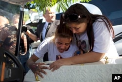 FILE - Adriana Maria dos Santos, mother of the late Vanessa do Santos, and a friend, Laisa, cry over Vanessa's casket during her burial in Rio de Janeiro, Brazil, July 6, 2017. The 10-year-old child was killed two days earlier after being hit in the head