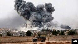 Tursko oklopno vozilo patrolira granicom sa Sirijom, dok se gust dim izdiže iznad Kobanija