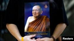 FILE - A man holds a portrait of Thailand's Supreme Patriarch, Somdet Phra Nyanasamvara Suvaddhana Mahathera, at Chulalongkorn Hospital in Bangkok, October 25, 2013.