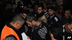 An Arab league observer, left, with orange vest, writes the names of freed Syrian prisoners as they are released from Adra Prison on the north-east outskirts of Damascus, Syria, January 15, 2012.