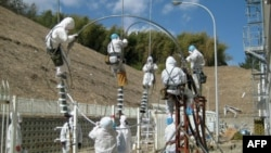 Các nhân viên đang sửa đường dây điện tại nhà máy điện hạt nhân Fukushima Daiichi ở Tomioka, ngày 24 tháng 3, 2011