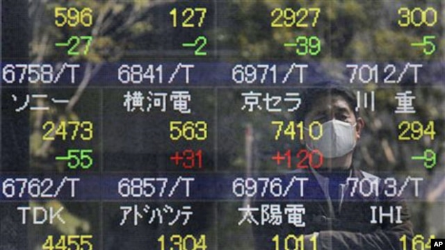 A reflection of a man who looks at the stock price board is seen in Tokyo,  March 17, 2011