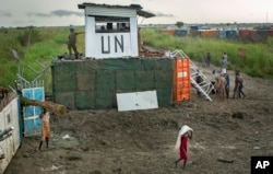 FILE - Displaced South Sudanese next to United Nations peacekeepers from Mongolia guarding the gate, at a makeshift camp at the United Nations Mission in South Sudan (UNMISS) base in the town of Bentiu, South Sudan, Sept. 22, 2014.