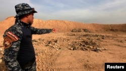 A member of Iraqi security forces gestures toward a mass grave in the town of Hammam al-Alil, which was seized from Islamic State, Nov. 9, 2016.