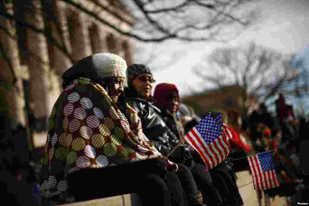 People sit on a wall at the National Mall for the ceremonial swearing-in on the West front of the U.S. Capitol in Washington January 21, 2013