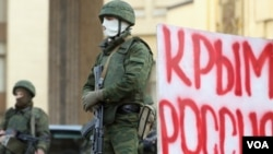 "Pria berseragam dan bersenjata tanpa tanda-tanda militer berjaga-jaga di gedung parlemen Krimea, Ukraina, dekat spanduk bertuliskan ""Krimea Rusia""."