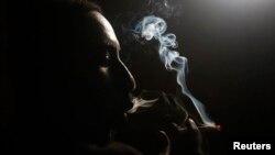 FILE - An addict smokes heroin in Lamu, Kenya, Nov. 21, 2014.