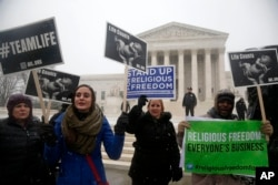 Demonstrators participate in a rally in front of the Supreme Court in Washington, Tuesday, March 25, 2014, as the court heard oral arguments in the challenges of President Barack Obama's health care law requirement that businesses provide their female employees with health insurance that includes access to contraceptives.