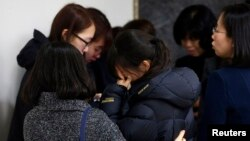Friends of victims who were killed when a resort building collapsed, react after they paid their tribute outside a group memorial altar in Gyeongju, about 375 km (235 miles) southeast of Seoul February 18, 2014. Ten people attending a welcoming party for