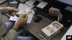 미국 달러와 이란 리알화를 환전 중인 은행 직원. (자료사진)