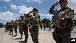 Soldados saludan los restos de tres camaradas que fueron asesinados en enfrentamientos con presuntos narcotraficantes a su arribo a una base de la Fuerza Aérea en Ciudad de Guatemala el jueves, 5 de septiembre, de 2019.