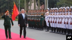 FILE - U.S. Defense Secretary Jim Mattis, right, and his Vietnamese counterpart, Ngo Xuan Lich, review an honor guard before heading for talks in Hanoi, Vietnam, Jan. 25, 2018.