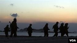 Sekelompok Marinir Korea Selatan berpatroli di sepanjang pantai pulau Yeonpyeong. Latihan di pulau ini akan kembali berlangsung pada hari Sabtu.