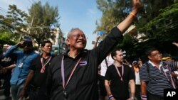 Suthep Thaugsuban, a former deputy premier leading the protest, waves to his supporters during an anti-government march to the Government complex in Bangkok, Thailand, Nov. 27, 2013.