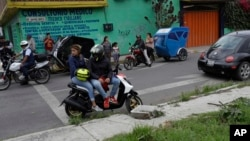 FILE - Residents and motorcycle taxi drivers stop to look at marines blocking the area where a suspected drug gang leader and seven others were killed in a shootout in the Tlahuac district of Mexico City, July 20, 2017.