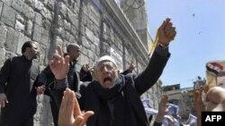 Một người ủng Syria ủng hộ chính phủ đang hô khẩu hiệu trong cuộc biểu tình sau buổi cầu nguyện thứ Sáu bên ngoài Ðền thờ Omayyad ở Damascus, Syria, ngày 15 tháng 4, 2011