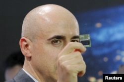 Investor Yuri Milner holds a Starchip, a microelectronic component spacecraft, during an announcement of the Breakthrough Starshot initiative with physicist Stephen Hawking and Avi Loeb in New York, April 12, 2016.