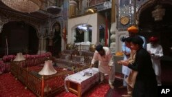FILE - People from Pakistan Sikh community visit their temple in Peshawar, Pakistan, Aug. 8, 2017. Today Sikhs are battling with the Pakistan government for ownership of dozens of Sikh temples, and while it is slow going they have managed to reclaim some of their temples.
