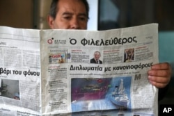 FILE - A man reads a Cypriot newspaper with a front page carrying a photo montage about Turkey's actions over Cyprus and international companies exploration for gas in the eastern Mediterranean in capital Nicosia, Cyprus, Feb. 13, 2018.