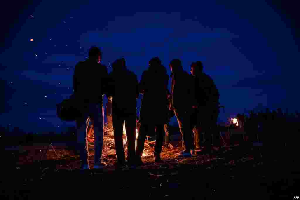 Migrants light a fire while camping along the Turkey-Greece border near Pazarkule, in Edirne district, Turkey.