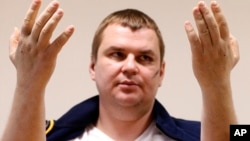 Ukrainian opposition activist Dmytro Bulatov holds up his hands that were pierced with nails, during a press conference in a hospital in Vilnius, Lithuania, Feb. 6, 2014.