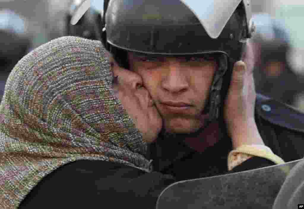 An Egyptian anti-government activist kisses a riot police officer following clashes in Cairo, Egypt, Friday, Jan. 28, 2011