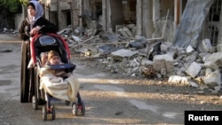 FILE - A woman, with her child in a stroller, stands along a damaged street in the besieged area of Homs, Syria.