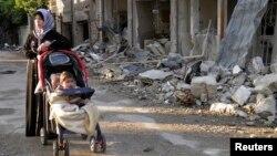 Phụ nữ và trẻ em đứng cạnh nhà cửa bị hư hại trong thành phố Homs, ngày 29/1/2014.