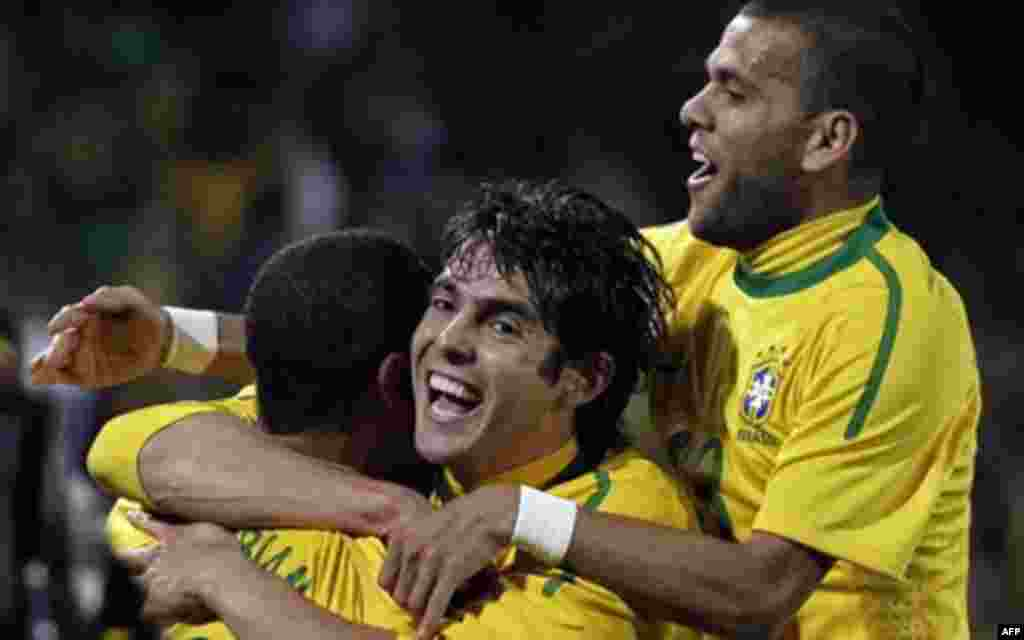 Brazil's Luis Fabiano, left, celebrates with Brazil's Kaka, center, and Brazil's Daniel Alves after scoring the second goal during the World Cup round of 16 soccer match between Brazil and Chile at Ellis Park Stadium in Johannesburg, South Africa, Monday,