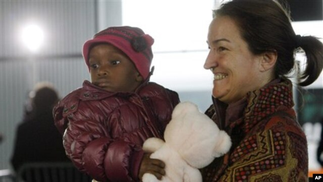 A French adoptive parent carries an orphan from Haiti at Roissy airport, outside of Paris, 22 Dec 2010