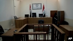FILE - An empty courtroom is seen at Nineveh Criminal Court, one of two counterterrorism courts in Iraq where suspected Islamic State militants and their associates are tried, in Tel Keif, Iraq, April 26, 2018.