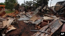 Distorted corrugate panels are scattered among debris of a burnt building in Thandwe, Rakhine State, western Burma, Oct. 2, 2013.