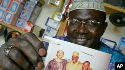FILE - Malik Obama, the older brother of US President Barack Obama holds an undated picture of Barak (L) and himself (C) and an unidentified friend in his shop in Siaya, eastern Kenya, Sept. 14, 2004.