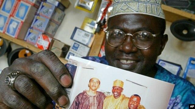 Foto de archivo en la que el medio-hermano del presidente Obama, Malik Obama, muestra una fotografía en la que aparece el presidente (izquierda), Malik (centro) y un amigo no identificado.